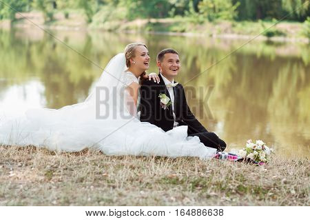Pure happiness. Young happy just married couple sitting in the grass laughing together