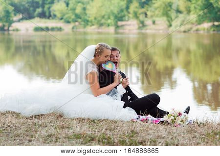 Sharing love. Cheerful newlywed husband and wife having fun sitting on the grass in the park biting heart shaped lollipop candy