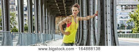 Outdoors fitness in Paris. Portrait of young sportswoman relaxing after workout on Pont de Bir-Hakeim bridge in Paris