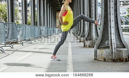 Outdoors fitness in Paris. Closeup on young sportswoman stretching on Pont de Bir-Hakeim bridge in Paris