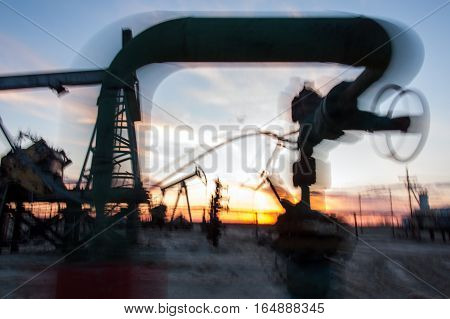 Work of oil pump jack and pipeline with valve on a oil field. Blurred motion.  Concept oil and gas industry.