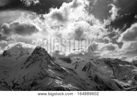 Black and white snow mountains in clouds. Caucasus Mountains region Dombay in winter.
