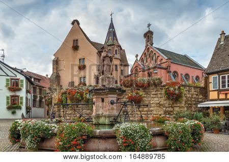 Main square with church and fountain with statue of pope Leo IX in Eguisheim Alsace France