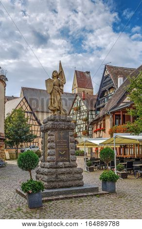 Stone statue of Jeanne d'Arc with standard and shield with her coat of arms Eguisheim Alsace France