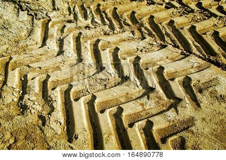 Off road tractor wheel tracks on road sand motoring background image. Industrial transport theme.