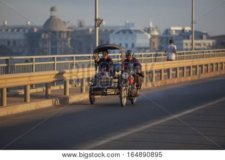 CHAMPASAK LAOS - NOV 23 : laos people traveling by motorcycle with side car on laos japan bridge in pakse distric on november 23 2013