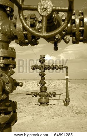 Wellhead with valve armature. Oil, gas industry. Toned sepia