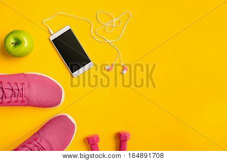 Still life of phone with headphones, sneakers, dumbbells on yellow background. Top view, flat lay. Mockup mobile phone. Sports and fitness background.