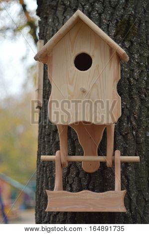 Wooden feeder handmade hanging in the park. Feeding the birds. Nature.