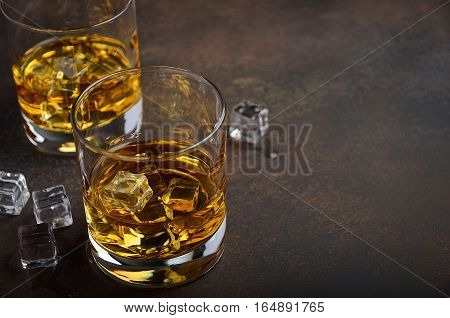 Glass of whiskey with ice on the old rusty background, copy space, horizontal