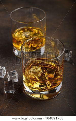 Glass of whiskey with ice on the old rusty background