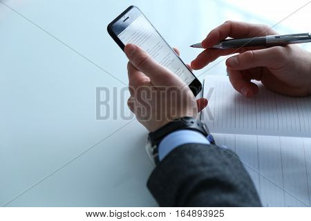 Businessman working on a desk. Freelance work at home office. Writing note on a book. Time racing.