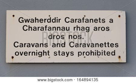 Sign prohibiting caravans staying overnight, in English and Welsh