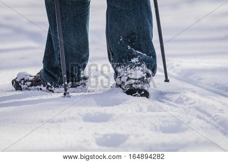 Closeup of person walking in snow with poles and one boot pointed