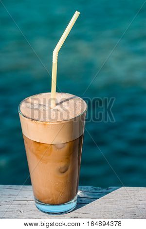 Two cups of coffee with ice cream on background of the sea. Morning coffee frappe by the sea. Vertical. Daylight.