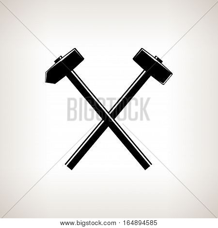 Silhouette of a crossed hammer and sledgehammer on  light background, black and white illustration