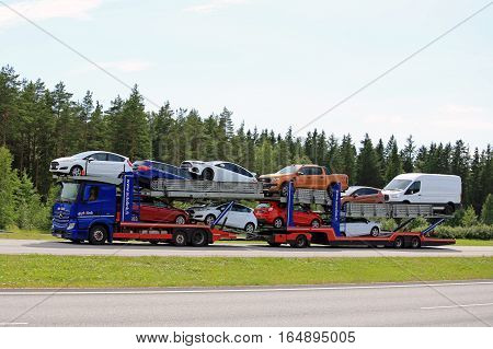 PAIMIO, FINLAND - JULY 1, 2016: Blue Mercedes-Benz Actros 1845 car transporter of Autolink transports new Ford vehicles along motorway at summer.
