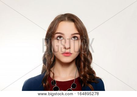 emotions people beauty and lifestyle concept - Eyes looking up. Beautiful happy teen girl looking up gray background