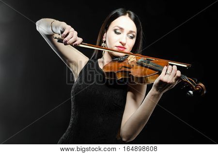 Young attractive woman in black dress playing on wooden violin on a black background. Horizontal photo