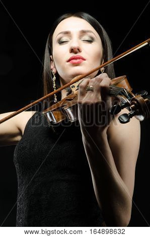 young woman who plays the violin with closed eyes smiling on a black background