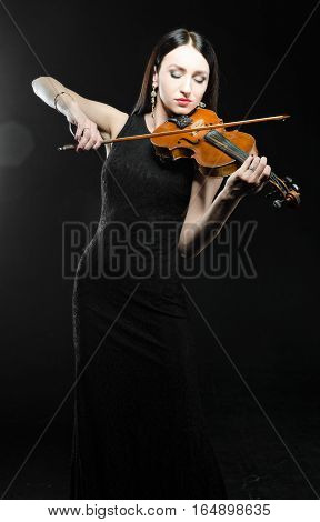 Woman in black dress playing in the wooden violin on a black background.