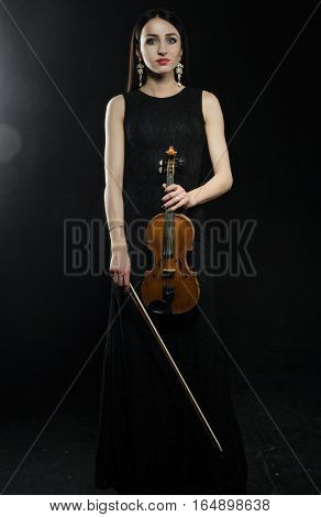Woman with a wooden violin in a black dress standing on black background looking at camera