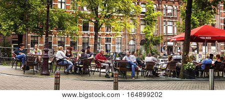 AMSTERDAM NETHERLANDS JULY 9 2016. People is relaxing and have a drink on a terrace along the canal in Amsterdam style of life in Amsterdam Netherlands.