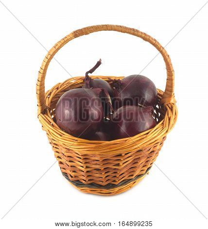 Purple onion turnip in brown round wicker basket isolated on white closeup