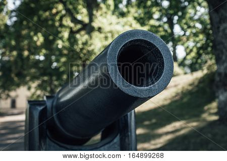 Black old cannon with a large caliber opening.
