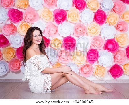 Spring Concept - Portrait Of Young Beautiful Woman Sitting Over Colorful Flowers Wall Background