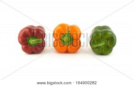 Three whole color ripe bell peppers in-line isolated on white close up