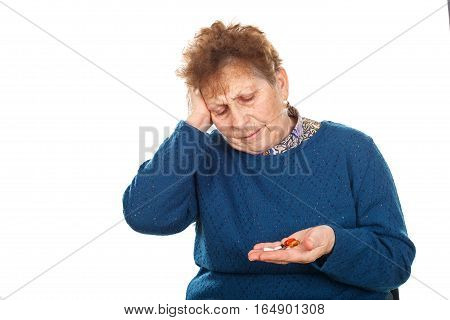 Picture of a senior woman having a headache holding her pills