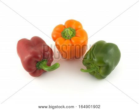 Three whole color ripe bell peppers isolated on white close up