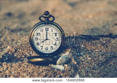 vintage pocket watch on sand beach , time concept