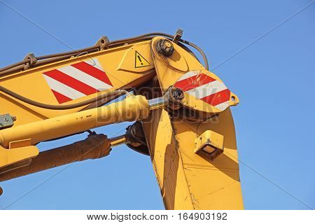 Detail of hydraulic bulldozer piston excavator arm on sky with clouds background