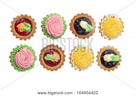Arrangement of Delicious Little Tarts with Colored Butter Cream Fruit Jam and Decoration In a Rows isolated on White background. Top View