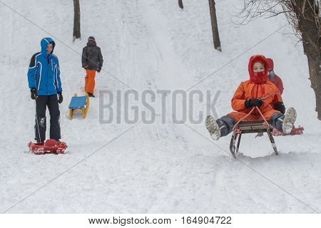 Bucharest Romania January 30 2014: Children sleighing on a hill in a park in Bucharest capital of Romania during a cold day. The meteorologist announced temperatures lower than normal for this period.