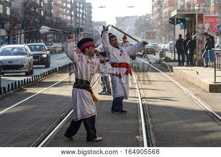 Bucharest Romania December 30 2012: Carolers dressed in national costumes are snapping the whips in a tram station in Bucharest.