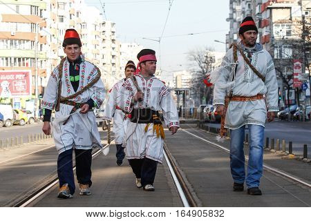 Bucharest Romania December 30 2012: Carolers dressed in national costumes and wearing whips are performing in a tram station in Bucharest.