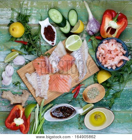 Arrangement of Raw Ingredients of Thai Fish Cakes with Vegetables Spices Sauces Prawns and Delicious Fillet of Salmon and Cod closeup on Cracked Wooden background. Top View