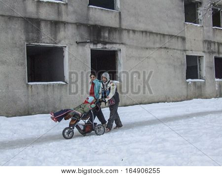 Bucharest Romania January 13 2008: Parents carry their disabled child on a go-cart in front of an abandoned building located at the periphery of Bucharest.