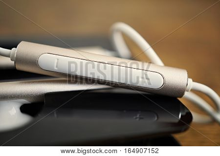 Macro detail of a silver volume controlling button (volume rocker) with plus and minus symbols attached to brand new white futuristic headphones