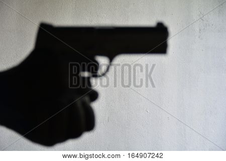 Shadow of hand holding handgun feeling violence and crime on grey background, silhouettes