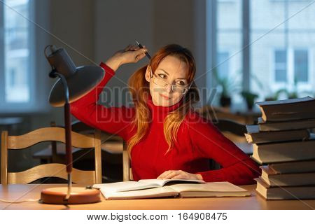 Girl Reading A Book In The Library Under The Lamp