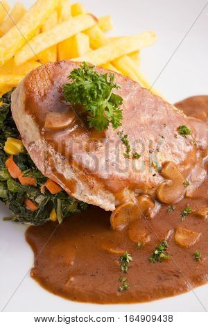 a dish of pork sirlion steak served with brown sauce and saute spinach and french fries in a nice dish.