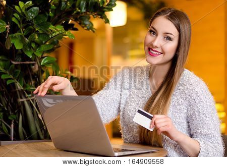 Model with blonde long hair in white sweater sitting on a chair in the office with beautiful stylish interior with laptop. Credit card in her hands, looking at the camera and smiling, on-line shopping.