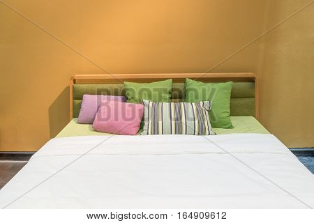 Bedroom interior with bed and colorful pillow of cosy home in modern design. Vintage bedroom.