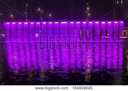 DUBAI UAE - NOV 28 2016: Purple Waterfall on Sheikh Zayed Bridge part of the Dubai Water Canal. Dubai United Arab Emirates
