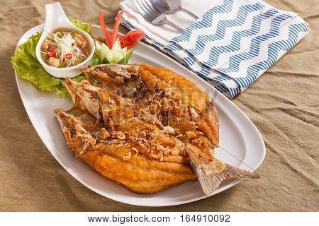 A dish of crispy Thai style deep fried whole sea bass fish served with spicy mango sauce.