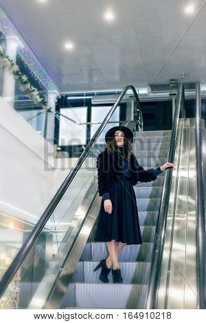The girl in hat and black dress on an escalator in a big store